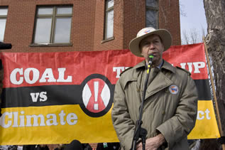 photo of a man speaking in front of a banner which reads in part: coal vs. climate !