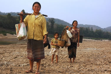 photo of women and a small child carrying burdens near a river