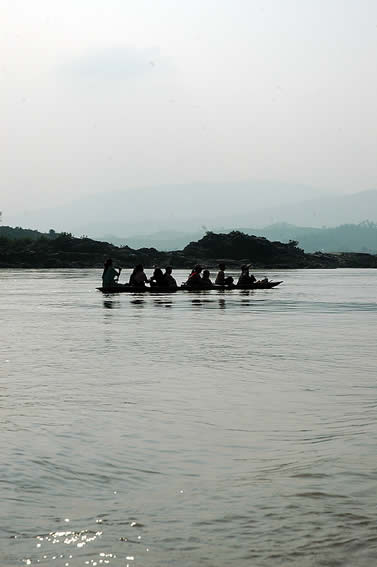 photo of an open boat with several people on it being paddled over a huge expans of river, mountains in the background