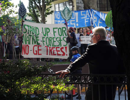 photo of a protest, in the foreground, a man in a suit watches