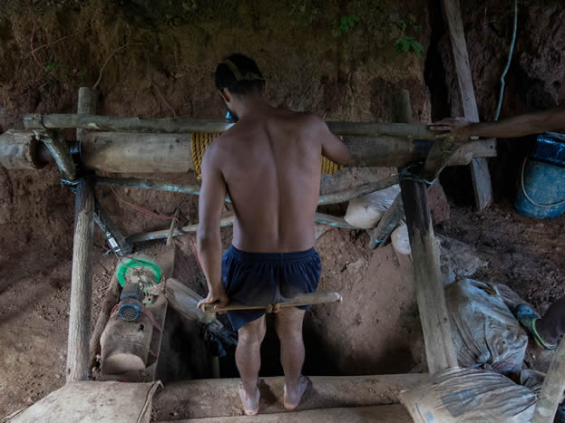 photo of a barefoot man in short pants sitting on a makeshift rope elevator about to descend into a mineshaft