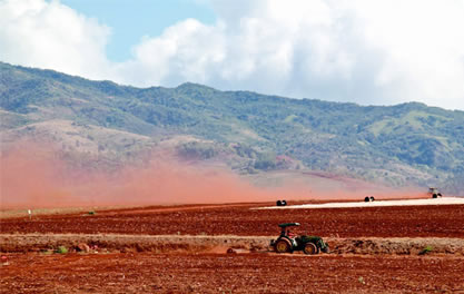 image of a tilled field, rust-colored dust flowing out behind a tractor; tropical mountains and clouds in the background