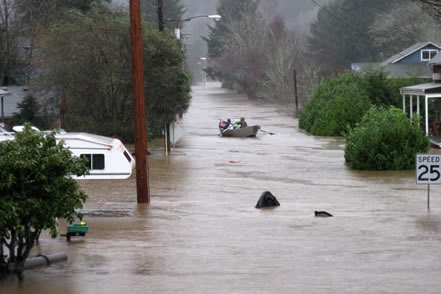photo of people paddling a boat on a deeply flooded residential street