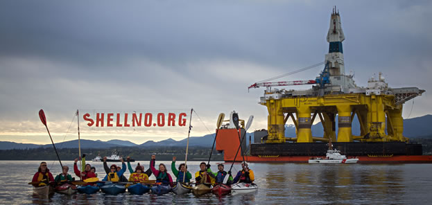 photo of kayakers near an oil platform, holding a sign that reads shellno.org