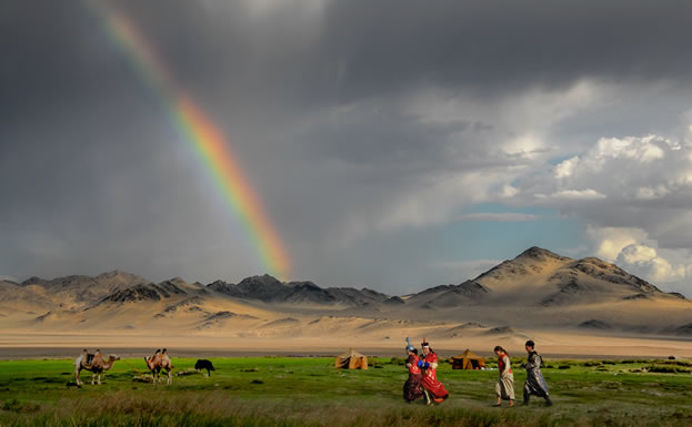 photo of people in the outdoors, with camels and a rainbow