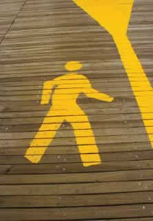photo of a stylized pedestrian glyph as painted on a walkway