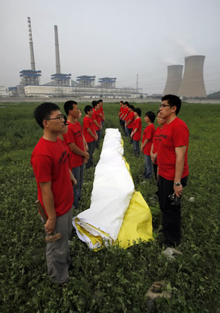 photo of people flanking a banner that is furled on the meadow near the cooling towers of a powerplant