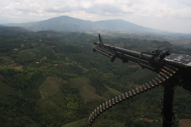 photo of a machine-gun pointed out the door of a helicopter, flying over a misty forested landscape