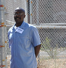photo of a man standing near a chainlink fence
