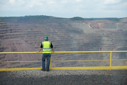 photo of a man in a safety vest looking over a collosal open pit mine