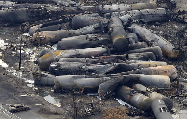 photo of the wreckage of many burned tanker railcars all in a heap