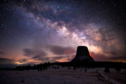 photo of the night sky, with the shadow of a stone monolith silhouetted