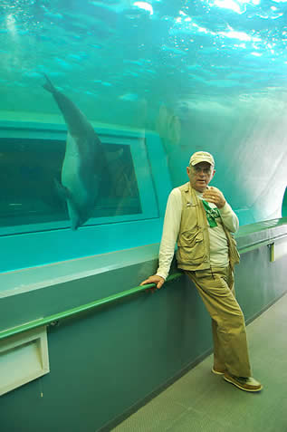 photo of a man in front of a sparse-looking tank, dolphin swimming inside