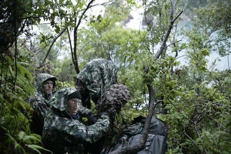 photo of men in full camouflage, in a rainy thicket of greenery