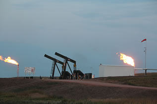 photo of large flares coming from stacks near oil well pumps