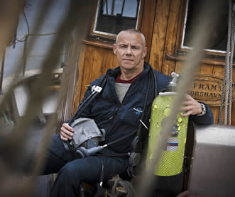 photo of a man sitting on a porch, he is holding a SCUBA tank