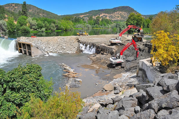 photo of construction vehicles operating at the shore of a river, dismantling a dam