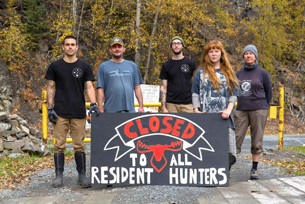photo of people blocking a road, sign reading, closed to all hunters