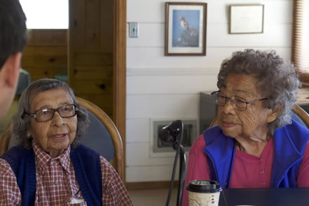 photo of two women elders speaking into a microphone