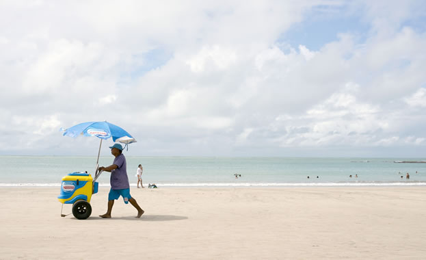 photo of a man pushing a food cart on a tropical beach
