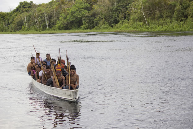 photo of many people on a boat in a rainforest river